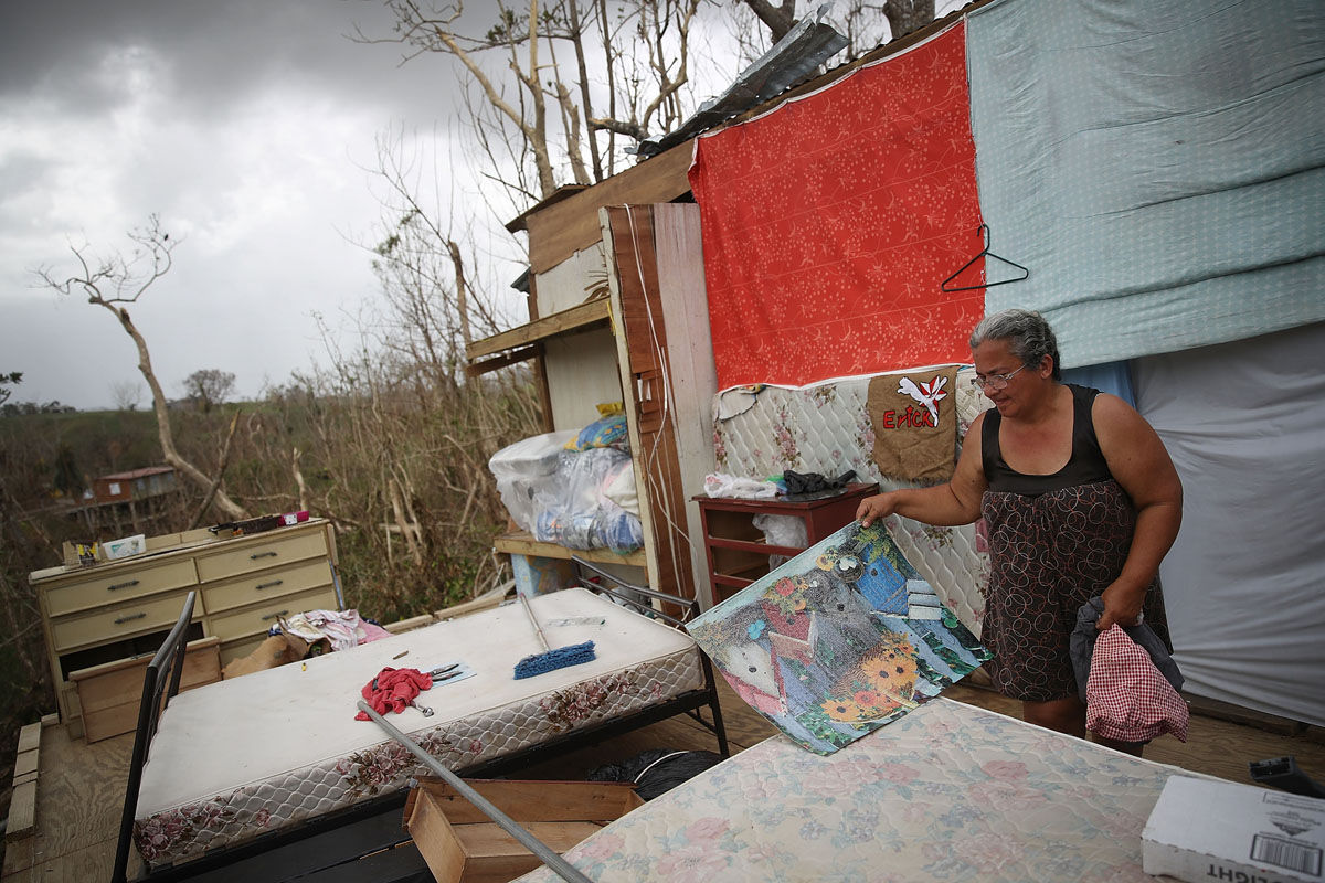 COROZAL, PUERTO RICO - SEPTEMBER 27: Yolanda Negron salvages what she can from what is left of her home that was destroyed when Hurricane Maria passed through on September 27, 2017 in Corozal, Puerto Rico. Puerto Rico experienced widespread, severe damage including most of the electrical, gas and water grids as well as agricultural destruction after Hurricane Maria, a category 4 hurricane, passed through.  (Photo by Joe Raedle/Getty Images)