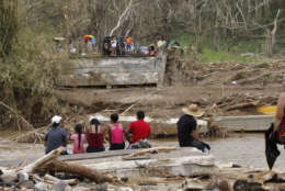 People sit on both sides of a destroyed bridge that crossed over the San Lorenzo de Morovis river, in the aftermath of Hurricane Maria, in Morovis, Puerto Rico, Wednesday, Sept. 27, 2017. A week since the passing of Maria many are still waiting for help from anyone from the federal or Puerto Rican government. But the scope of the devastation is so broad, and the relief effort so concentrated in San Juan, that many people from outside the capital say they have received little to no help. (AP Photo/Gerald Herbert)