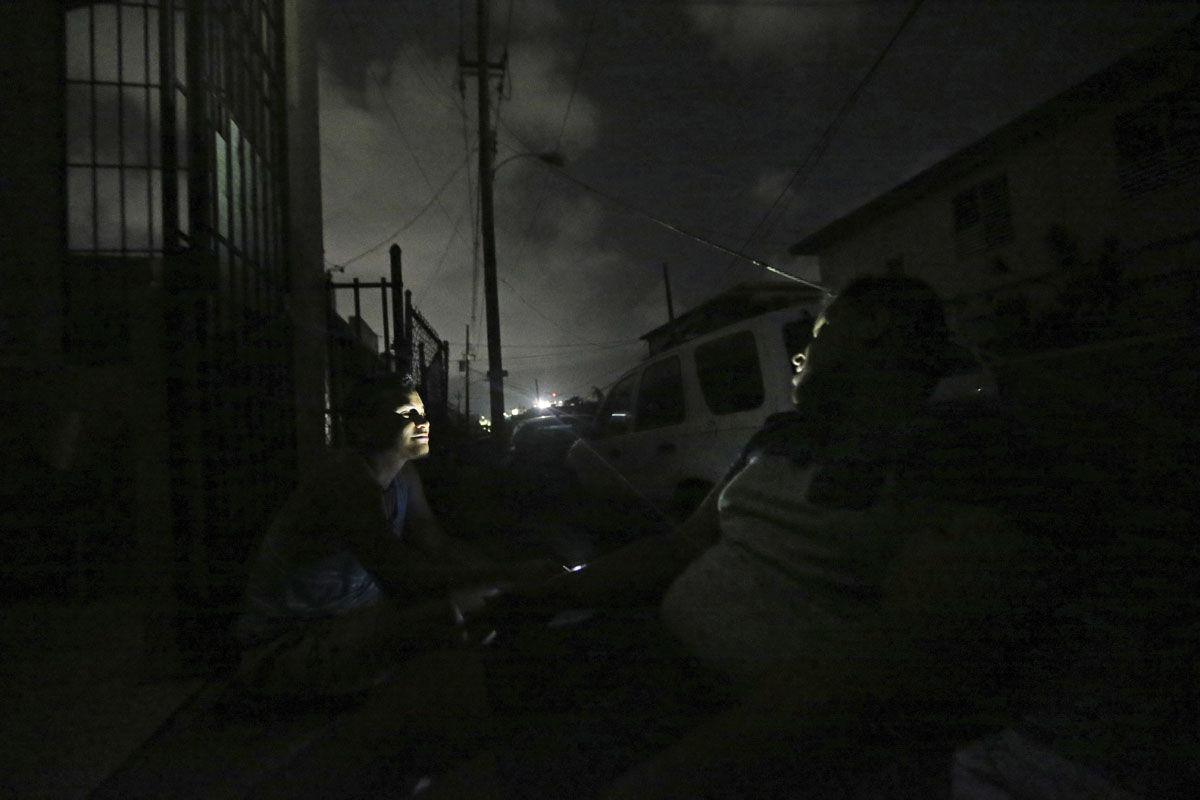 Steven Sands, left, talks with Alejandro Garcia, coping with the lack of electricity in the aftermath of Hurricane Maria in San Juan, Puerto Rico, Wednesday, Sept. 27, 2017. (AP Photo/Gerald Herbert)