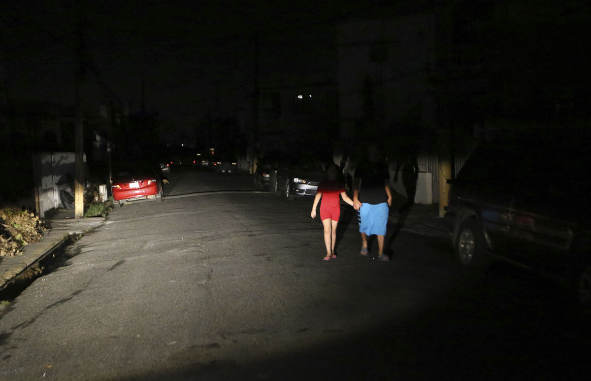 Raphael Urena and Viviana Urena, illuminated by the headlights from a car, walk down a residential street, as most of Puerto Rico copes without electricity, in the aftermath of Hurricane Maria in San Juan, Puerto Rico, Wednesday, Sept. 27, 2017. (AP Photo/Gerald Herbert)