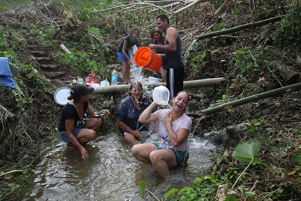 COROZAL, PUERTO RICO - SEPTEMBER 27:  People bathe in spring water since they have no running water in their homes since Hurricane Maria passed through on September 27, 2017 in Corozal, Puerto Rico.  Puerto Rico experienced widespread damage including most of the electrical, gas and water grid as well as agriculture after Hurricane Maria, a category 4 hurricane, passed through.  (Photo by Joe Raedle/Getty Images)
