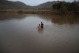 MOROVIS, PUERTO RICO - SEPTEMBER 27:  Hector Ojeda and Sonia Robles and Tony Ojeda cross a river on foot after the bridge was washed away when Hurricane Maria passed through on September 27, 2017 in Morovis, Puerto Rico.  Puerto Rico experienced widespread damage including most of the electrical, gas and water grid as well as agriculture after Hurricane Maria, a category 4 hurricane, passed through.  (Photo by Joe Raedle/Getty Images)