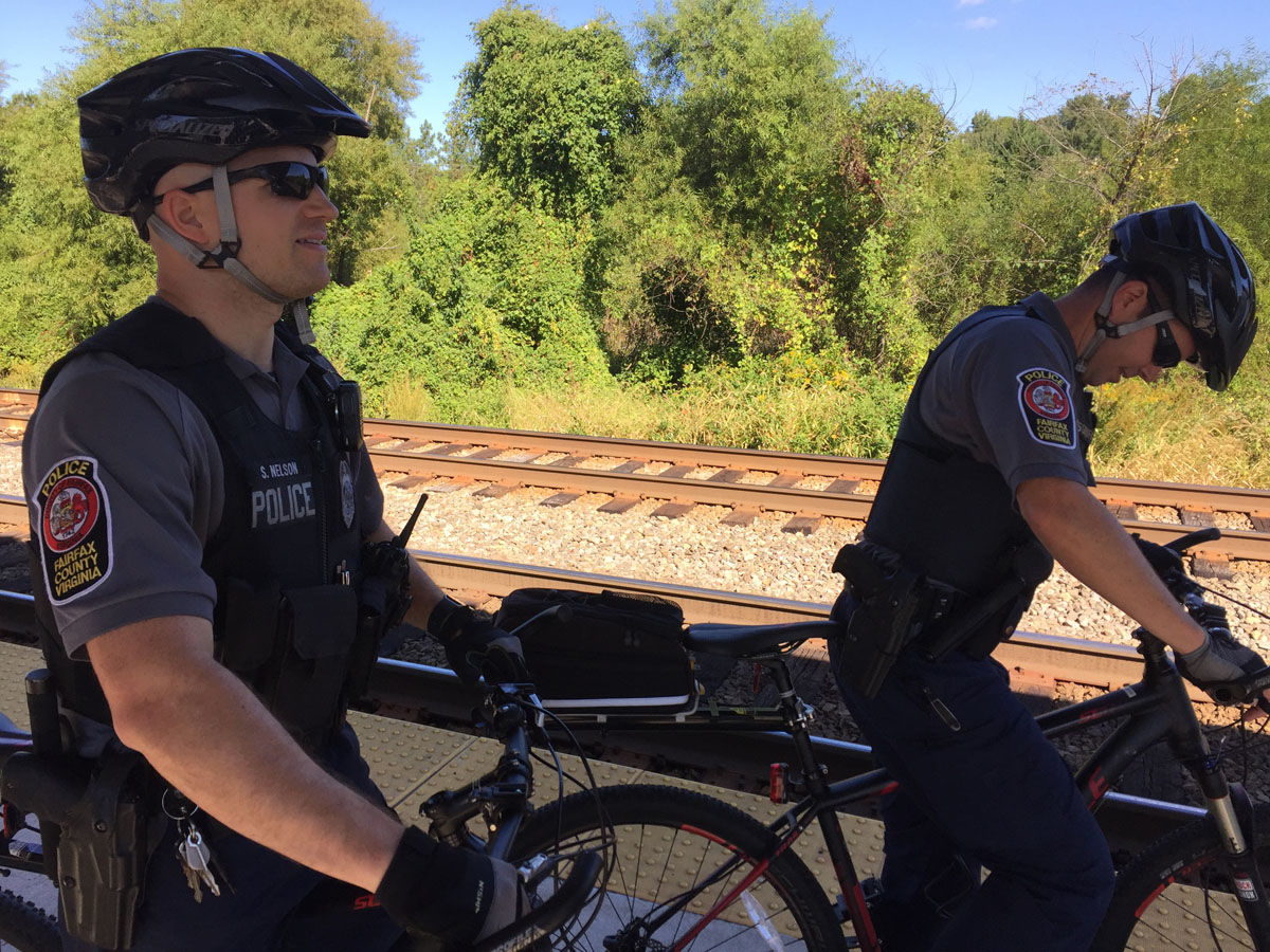 Fairfax County officers Shay Nelson (left) and Chris Cosgriff, on the station platform. The officers patrol areas of the track where people are known to cross. (WTOP/John Aaron)