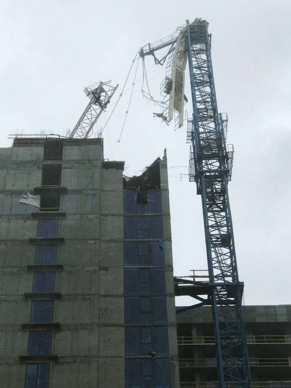 A crane atop a high-rise under construction in downtown Miami collapsed Sunday, Sept. 10, 2017, amid strong winds from Hurricane Irma.  The crane collapsed in a bayfront area filled with hotels and high-rise condo and office buildings, near AmericanAirlines Arena, according to a tweet from the City of Miami. (Gideon J. Ape via AP)