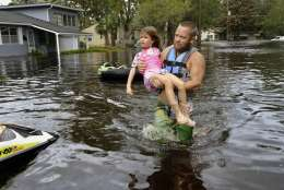 Tommy Nevitt carries Miranda Abbott, 6, through floodwater caused by Hurricane Irma on the west side of Jacksonville, Fla., Monday, Sept. 11 2017. (Dede Smith/The Florida Times-Union via AP)