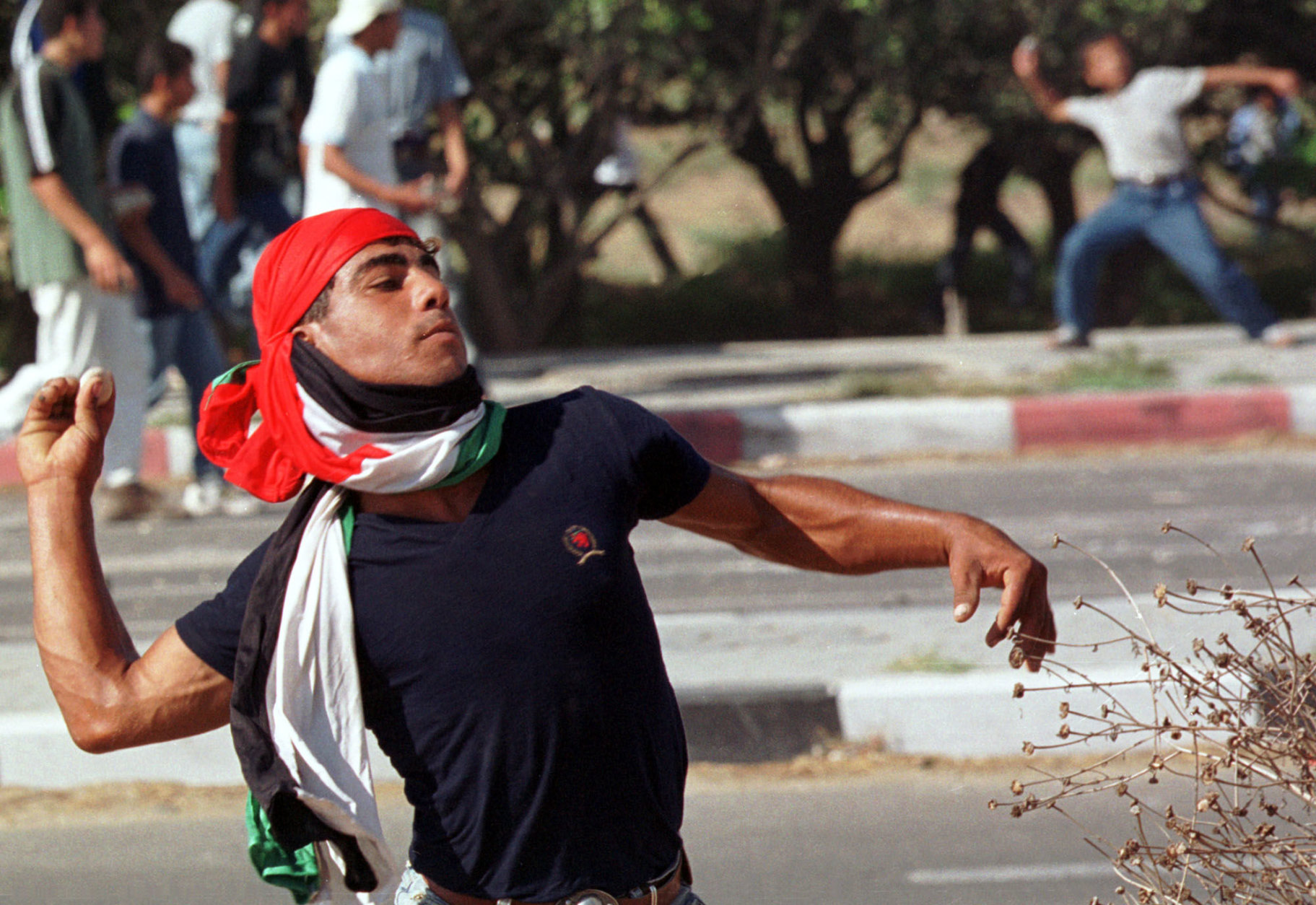 A man with the Palestinian flag wrapped around his head, throws stones during clashes between Paletinians and Israeli soldiers at the entrance of Israeli Netzarim Jewish settlement crossing, in the southern Gaza City, Saturday, Sept. 30, 2000.  Palestinian youths stoned Israelis a day after Israel riot police stormed a major Muslim shrine in Jerusalem killing  six Palestinians. (AP Photo/Adel Hana)