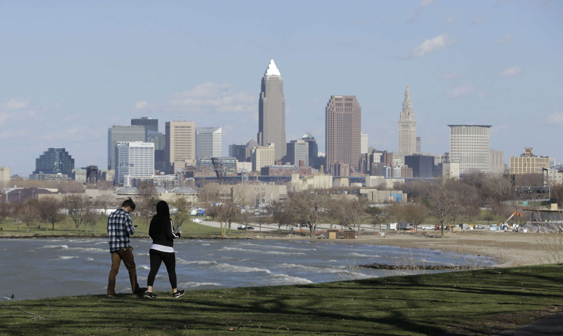 A couple walk along the shores of Lake Erie, Wednesday, March 8, 2017, in Cleveland. (AP Photo/Tony Dejak)