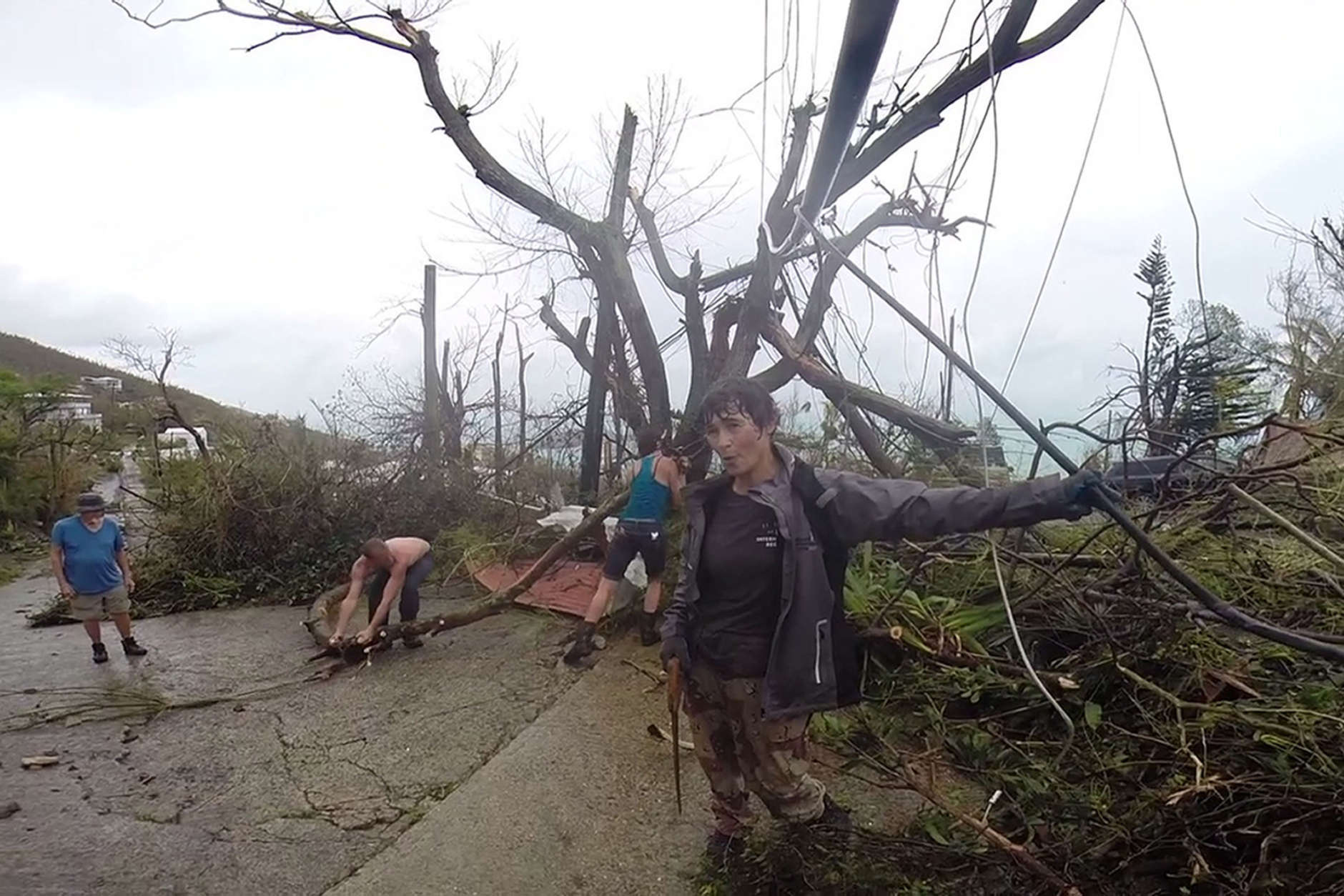 In this image made from video, neighbors clear debris from the road in St. Thomas, U.S. Virgin Islands, Thursday, Sept. 7, 2017. Hurricane Irma weakened slightly Thursday with sustained winds of 175 mph, according to the National Hurricane Center. The storm boasted 185 mph winds for a more than 24-hour period, making it the strongest storm ever recorded in the Atlantic Ocean. The storm was expected to arrive in Cuba by Friday. It could hit the Florida mainland by late Saturday, according to hurricane center models. (AP Photo/Ian Brown)