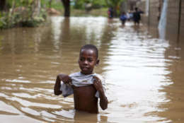 A boy walks in the floodwaters of Hurricane Irma, in Fort-Liberte, Haiti, Friday Sept. 8, 2017. Irma rolled past the Dominican Republic and Haiti and battered the Turks and Caicos Islands early Friday with waves as high as 20 feet (6 meters). ( AP Photo/Dieu Nalio Chery)