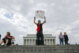 """Fonz Tobin, 25, from Albuquerque, N.M., holds up a sign in front of the Lincoln Memorial in Washington, as he joins other supporters of the rap group Insane Clown Posse, during a rally, Saturday, Sept. 16, 2017, to protest and demand that the FBI rescind its classification of the juggalos as """"loosely organized hybrid gang.""""(AP Photo/Pablo Martinez Monsivais)"""
