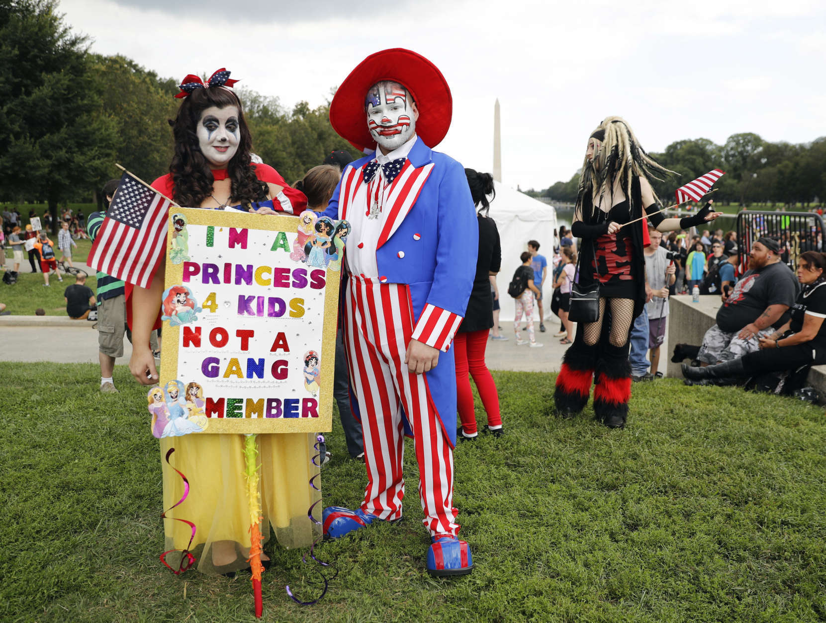 """Theresa Lindsey, left, dressed as Snow White and Timothy Schlarmann, center, dressed as Uncle Sam, both from southern California, join other juggalos, as supporters of the rap group Insane Clown Posse are known, in front of the Lincoln Memorial in Washington during a rally, Saturday, Sept. 16, 2017, to protest and demand that the FBI rescind its classification of the juggalos as """"loosely organized hybrid gang."""" (AP Photo/Pablo Martinez Monsivais)"""