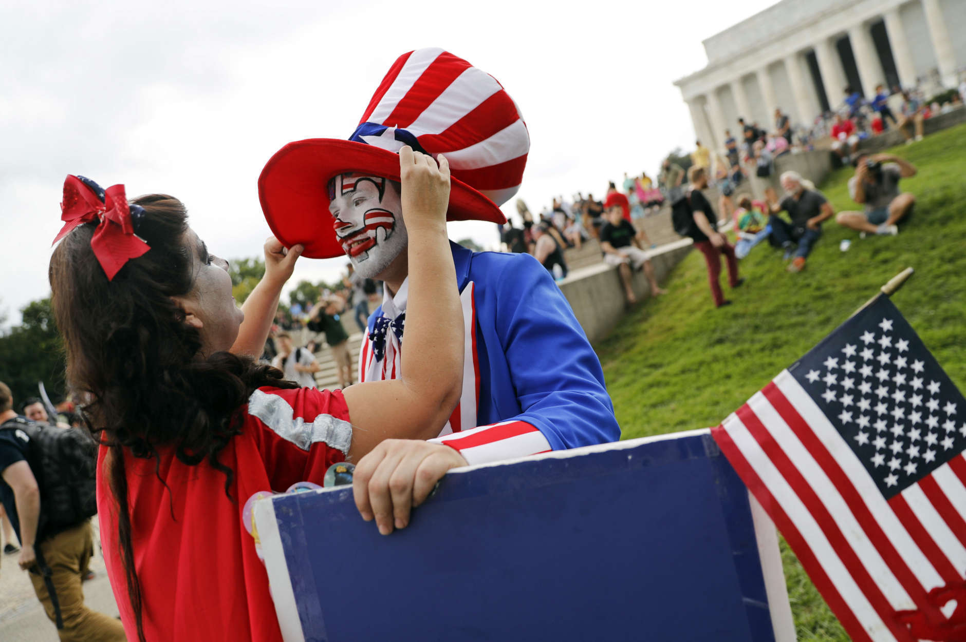 """Theresa Lindsey, left, dressed as Snow White helps Timothy Schlarmann, center, dressed as Uncle Sam, who are from southern California, with his costume as they join other juggalos, as supporters of the rap group Insane Clown Posse are known, in front of the Lincoln Memorial in Washington during a rally, Saturday, Sept. 16, 2017, to protest and demand that the FBI rescind its classification of the juggalos as """"loosely organized hybrid gang."""" (AP Photo/Pablo Martinez Monsivais)"""