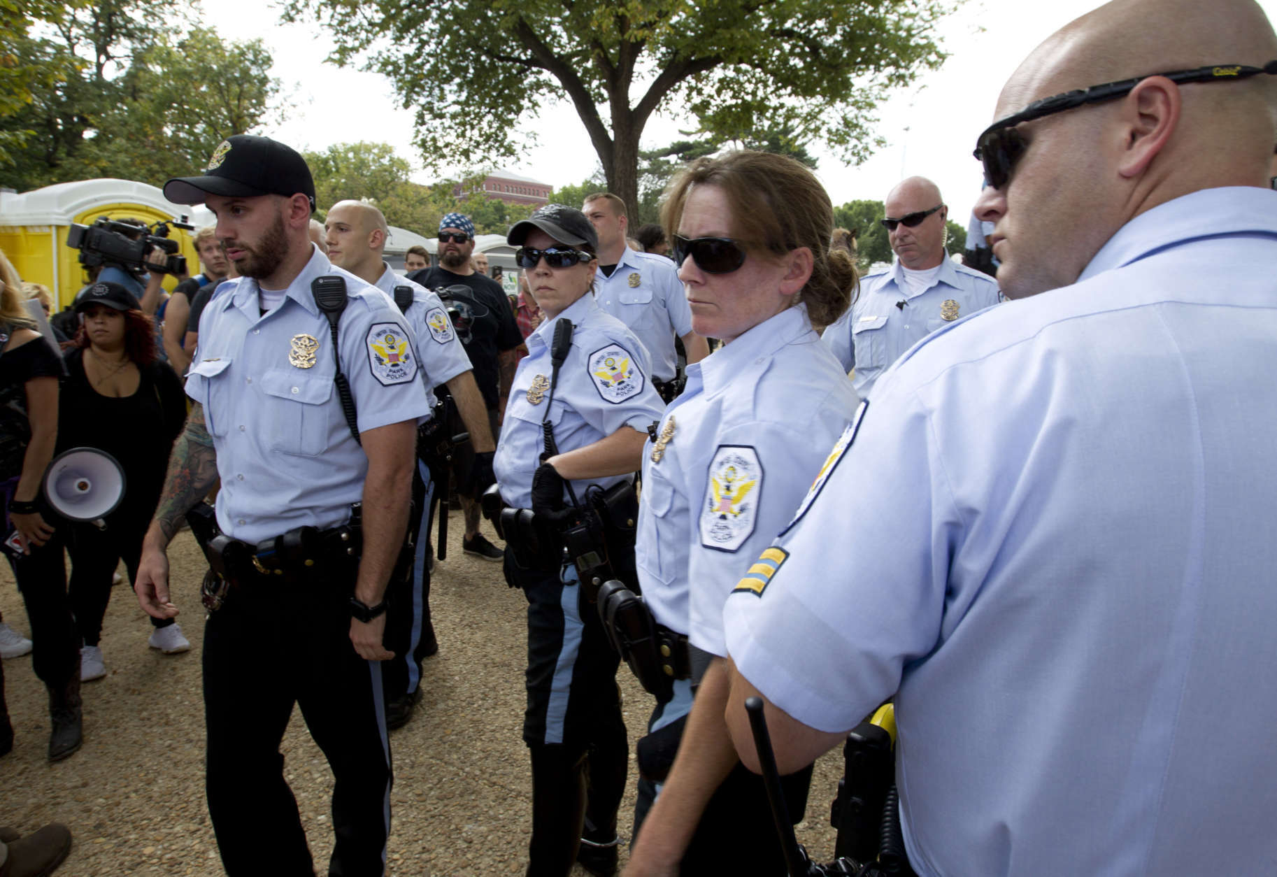 """Park police officers watch demonstrators during a rally on the National Mall in Washington, Saturday, Sept. 16, 2017, in support of President Donald Trump in what organizers are calling 'The Mother of All Rallies."""" ( AP Photo/Jose Luis Magana)"""