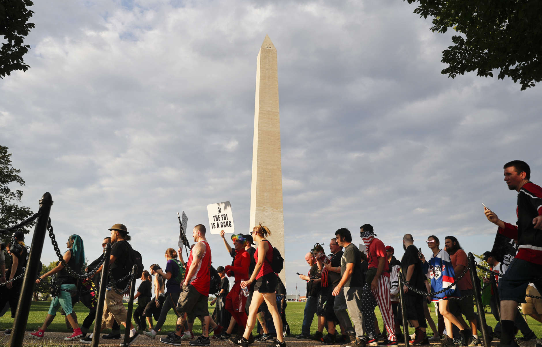 """Juggalos, as supporters of the rap group Insane Clown Posse are known, march past the Washington Monument as they head towards the Lincoln Memorial in Washington during a rally, Saturday, Sept. 16, 2017. The event was held to demand that the FBI rescind its classification of the juggalos as a """"loosely organized hybrid gang."""" (AP Photo/Pablo Martinez Monsivais)"""