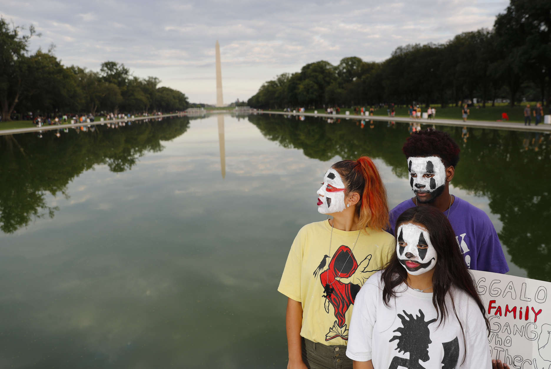 """From left, sisters Melina, 17, and Tiffany Baker, 12, and Jajuan Dunkins, 17, join other juggalos, as supporters of the rap group Insane Clown Posse are known, in front of the Reflecting Pool along the National Mall in Washington during a rally, Saturday, Sept. 16, 2017. The event was to demand that the FBI rescind its classification of the juggalos as """"loosely organized hybrid gang."""" (AP Photo/Pablo Martinez Monsivais)"""