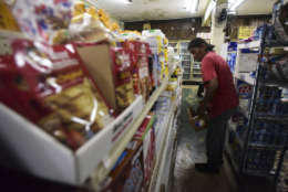 Residents from Juana Matos buy groceries at Catano Mini Market in the middle of a supply shortage caused by the passage of Hurricane Maria, in Catano, Puerto Rico, Wednesday, Sept. 27, 2017. The aftermath of the powerful storm has resulted in a near-total shutdown of the Puerto Rican economy that could last for weeks and has many people running seriously low on cash and deeply concerned that it will become even harder to survive on this storm-ravaged island. (AP Photo/Carlos Giusti)