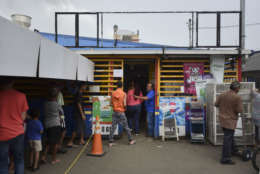 Residents from Juana Matos wait in line to buy groceries at Catano Mini Market in the middle of a supply shortage caused by the passage of Hurricane Maria, in Catano, Puerto Rico, Wednesday, September 27, 2017. The aftermath of the powerful storm has resulted in a near-total shutdown of the Puerto Rican economy that could last for weeks and has many people running seriously low on cash and deeply concerned that it will become even harder to survive on this storm-ravaged island. (AP Photo/Carlos Giusti)