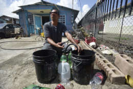 Toa Alta resident Jose Ramos fills buckets with water at a family member's home in the Juana Matos community one week after Hurricane Maria hit Catano, Puerto Rico, Thursday, Sept. 28, 2017. The aftermath of the powerful storm has resulted in a near-total shutdown of the U.S. territory's economy that could last for weeks and has many people running seriously low on cash and worrying that it will become even harder to survive on this storm-ravaged island. (AP Photo/Carlos Giusti)