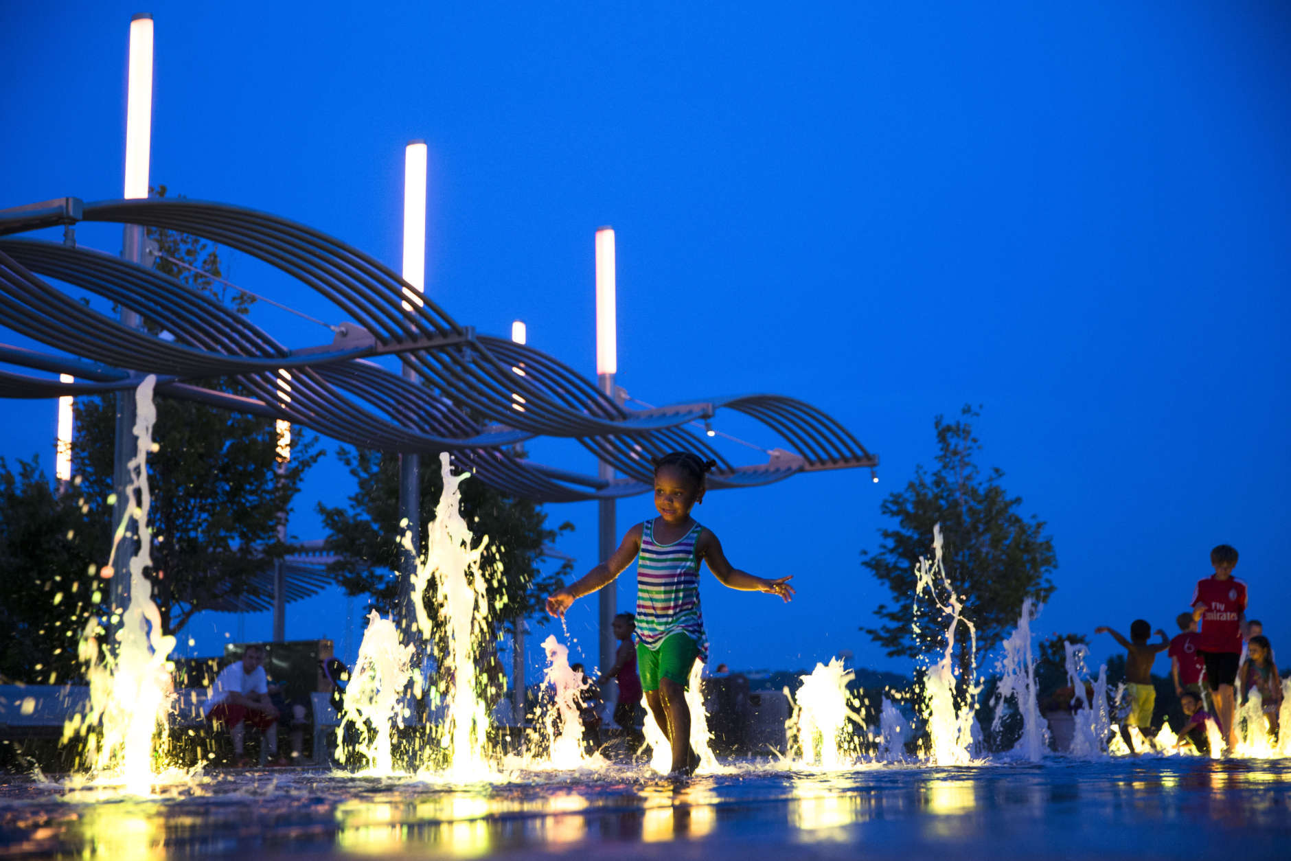 Children play in an illuminated fountain at Smale Riverfront Park in Cincinnati, Monday, June 22, 2015. The park is part of a five-phase revitalization of the Ohio riverfront as the downtown area undergoes a resurgence with investors and businesses moving into once vacant lots and buildings. (AP Photo/John Minchillo)