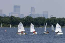 Sailing enthusiasts navigate the waters of Lake Calhoun as the Minneapolis skyline rises, shrouded in hazy skies because of elevated levels of fine particle pollution, likely the result of smoke from Canadian forest fires,Thursday, July 11, 2013. Air pollution levels are expected to remain elevated through Friday evening, July 12.  (AP Photo/Jim Mone)