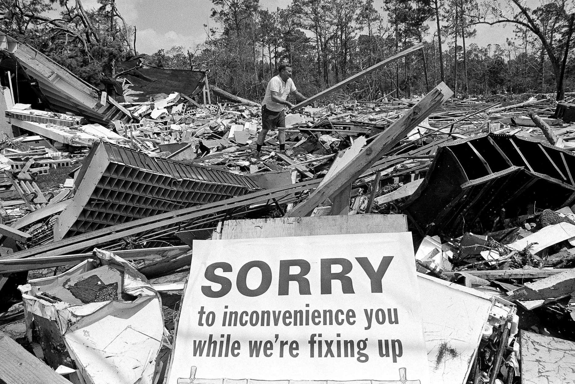 Service station owner H.A. Torgerson moves debris in what had been the town post office, next door to his station in Waveland, Miss., Sept. 11, 1969. Hurricane Camille had devastated the area about three weeks earlier. (AP Photo/Jack Thornell)