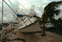 FILE - In this Aug. 24, 1992 file photo, a sailboat sits on a sidewalk at Dinner Key in Miami after it was washed ashore by Hurricane Andrew. Several days after it almost dissipated, Andrew rapidly strengthened and was a Category 4 storm at landfall in Homestead, Fla. The Hurricane Center measured a peak wind gust of 164 mph. Andrew continued into the Gulf of Mexico before reaching the central Louisiana coast as a Category 3 hurricane. Andrew was blamed for 23 deaths in the U.S. and three deaths in the Bahamas and caused an estimated $26.5 billion in damage in the United States. (AP Photo/Terry Renna, File)