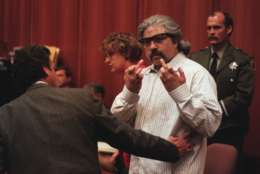 Richard Allen Davis, found guilty of the murder of Polly Klaas in San Jose on Tuesday, June 18, 1996, gestures toward the television camera after the verdict.  He is restrained by his lawyer defense counsel Barry Collins.  Behind is his other attorney Lorena Chandler. (AP Photo/John Burgess)