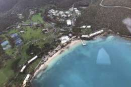 This photo provided on Friday, Sept. 8, 2017, shows storm damage in the aftermath of Hurricane Irma in St. John's Caneel Bay in the U.S. Virgin Islands. Irma scraped Cuba's northern coast Friday on a course toward Florida, leaving in its wake a ravaged string of Caribbean resort islands strewn with splintered lumber, corrugated metal and broken concrete. (Caribbean Buzz Helicopters via AP)