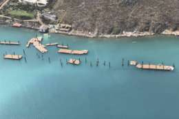 CORRECTS DAY - This photo provided on Friday, Sept. 8, 2017, shows the docks damaged by Hurricane Irma at Virgin Gorda's Yacht Club Costa Smeralda in the British Virgin Islands. Irma scraped Cuba's northern coast Friday on a course toward Florida, leaving in its wake a ravaged string of Caribbean resort islands strewn with splintered lumber, corrugated metal and broken concrete. (Caribbean Buzz Helicopters via AP)