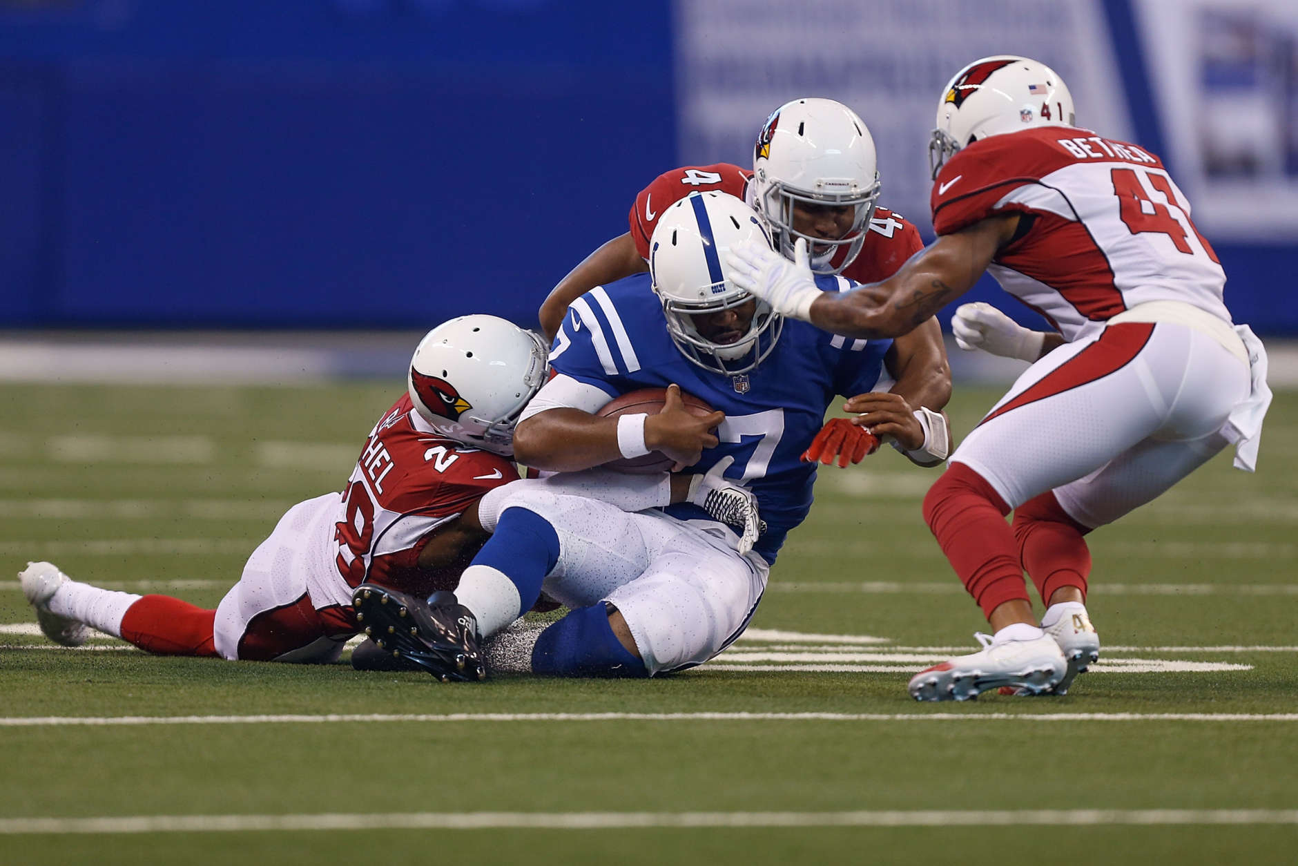 INDIANAPOLIS, IN - SEPTEMBER 17:  Jacoby Brissett #7 of the Indianapolis Colts is tackled by Justin Bethel #28, Haason Reddick #43 and Antoine Bethea #41 of the Arizona Cardinals during the first half at Lucas Oil Stadium on September 17, 2017 in Indianapolis, Indiana.  (Photo by Michael Reaves/Getty Images)