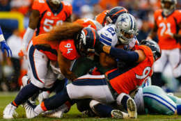 DENVER, CO - SEPTEMBER 17:  Nose tackle Domata Peko #94 and defensive tackle Adam Gotsis #99 of the Denver Broncos tackle running back Ezekiel Elliott #21 of the Dallas Cowboys in the first half at Sports Authority Field at Mile High on September 17, 2017 in Denver, Colorado. (Photo by Justin Edmonds/Getty Images)