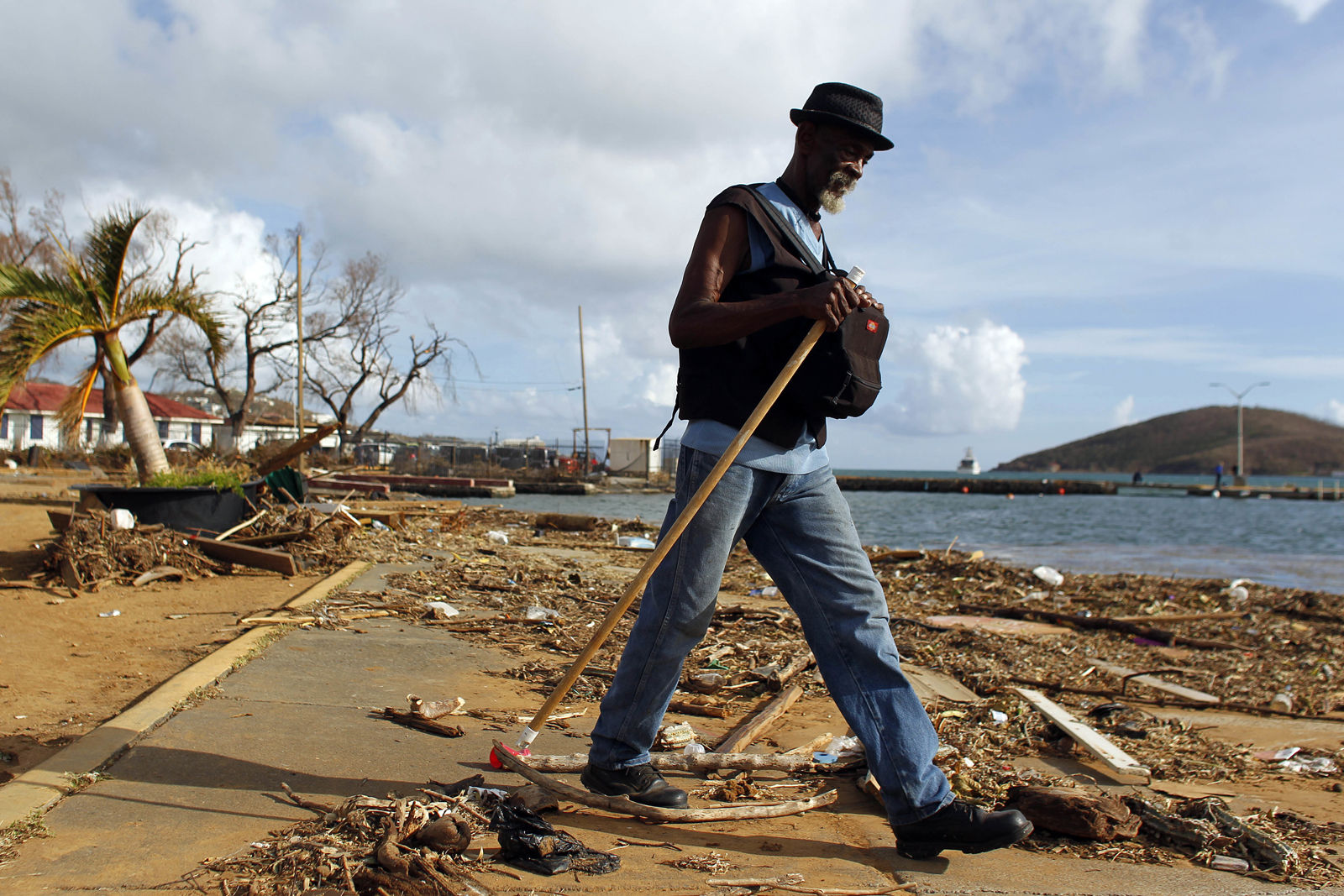 A man walks past debris caused by Hurricane Irma in Charlotte Amalie, St. Thomas, U.S. Virgin Islands, Sunday, Sept. 10, 2017.  The storm ravaged such lush resort islands as St. Martin, St. Barts, St. Thomas, Barbuda and Anguilla. (AP Photo/Ricardo Arduengo)
