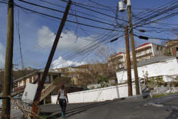 A woman walks under affected power lines after the passage of Hurricane Irma in Charlotte Amalie, St. Thomas, U.S. Virgin Islands, Sunday, Sept. 10, 2017.  The storm ravaged such lush resort islands as St. Martin, St. Barts, St. Thomas, Barbuda and Anguilla. (AP Photo/Ricardo Arduengo)