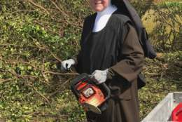 In this Tuesday, Sept. 12, 2017, photo provided by the Miami-Dade Police Department, Sister Margaret Ann holds a chain saw near Miami, Fla. Police said the nun was cutting trees to clear the roadways around Archbishop Coleman Carrol High School in the aftermath of Hurricane Irma. (Miami-Dade Police Department via AP)