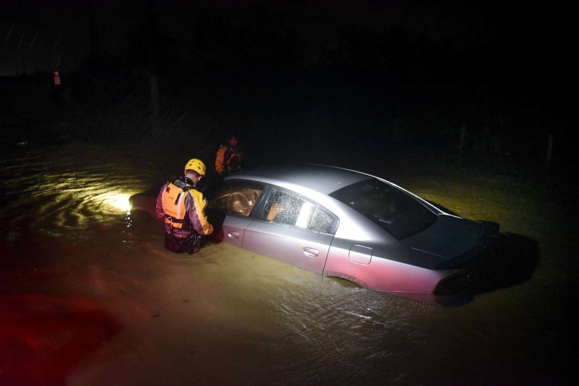 Rescue staff from the Municipal Emergency Management Agency investigate an empty flooded car during the passage of Hurricane Irma through the northeastern part of the island in Fajardo, Puerto Rico, Wednesday, Sept. 6, 2017. Hurricane Irma lashed Puerto Rico with heavy rain and powerful winds, leaving nearly 900,000 people without power as authorities struggled to get aid to small Caribbean islands already devastated by the historic storm. (AP Photo/Carlos Giusti)