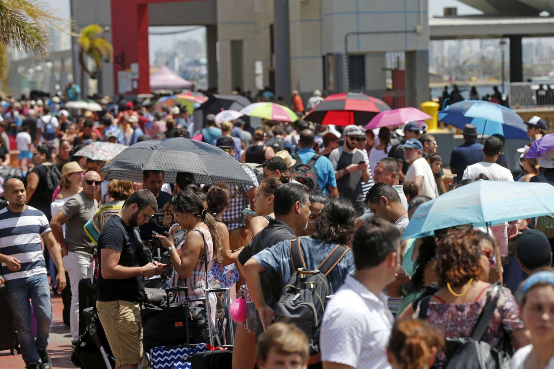 Thousands of people evacuating Puerto Rico line up to get on a cruise ship in the aftermath of Hurricane Maria in San Juan, Puerto Rico, Thursday, Sept. 28, 2017. The aftermath of the powerful storm has resulted in a near-total shutdown of the U.S. territory's economy that could last for weeks and has many people running seriously low on cash and worrying that it will become even harder to survive on this storm-ravaged island. (AP Photo/Gerald Herbert)