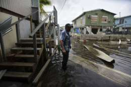 Juana Matos resident Hector Rosa walks through a flooded area after the passing of Hurricane Maria, in Puerto Rico, Wednesday, September 27, 2017. Since the devastating impact of said hurricane, the supply line of goods in general was interrupted in the US territory, causing endless rows in gas stations and comercial centers. (AP Photo/Carlos Giusti)