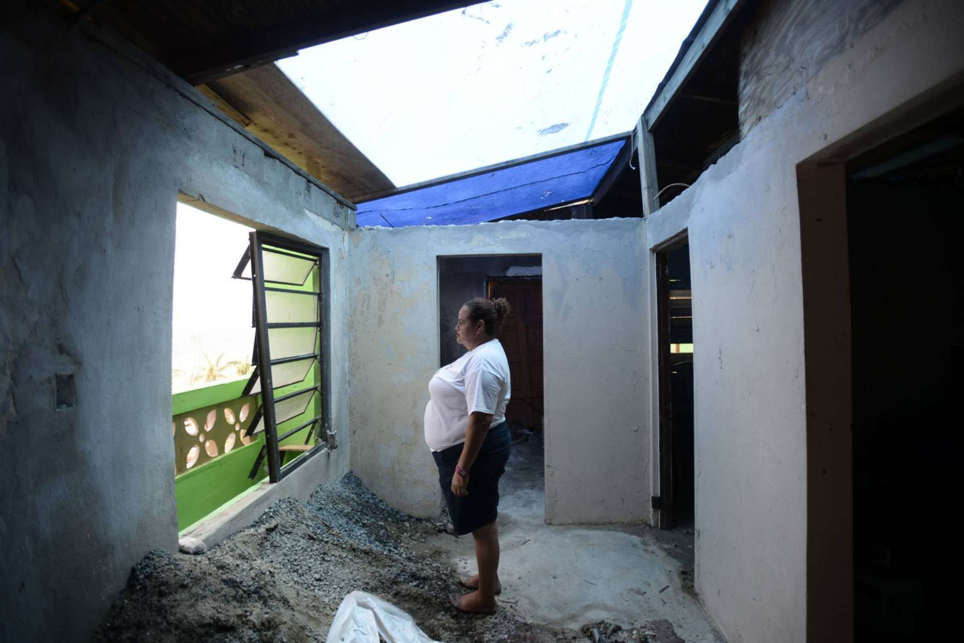 La Perla resident Maritza Rosado stands inside her roofless home after Hurricane Maria, in San Juan, Puerto Rico, Monday, Sept. 25, 2017. The island territory of more than 3 million U.S. citizens is reeling in the devastating wake of Hurricane Maria. (AP Photo/Carlos Giusti)