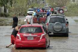 Residents drive through a flooded road after the passing of Hurricane Maria, in Toa Baja, Puerto Rico, Friday, September 22, 2017. Because of the heavy rains brought by Maria, thousands of people were evacuated from Toa Baja after the municipal government opened the gates of the Rio La Plata Dam. (AP Photo/Carlos Giusti)