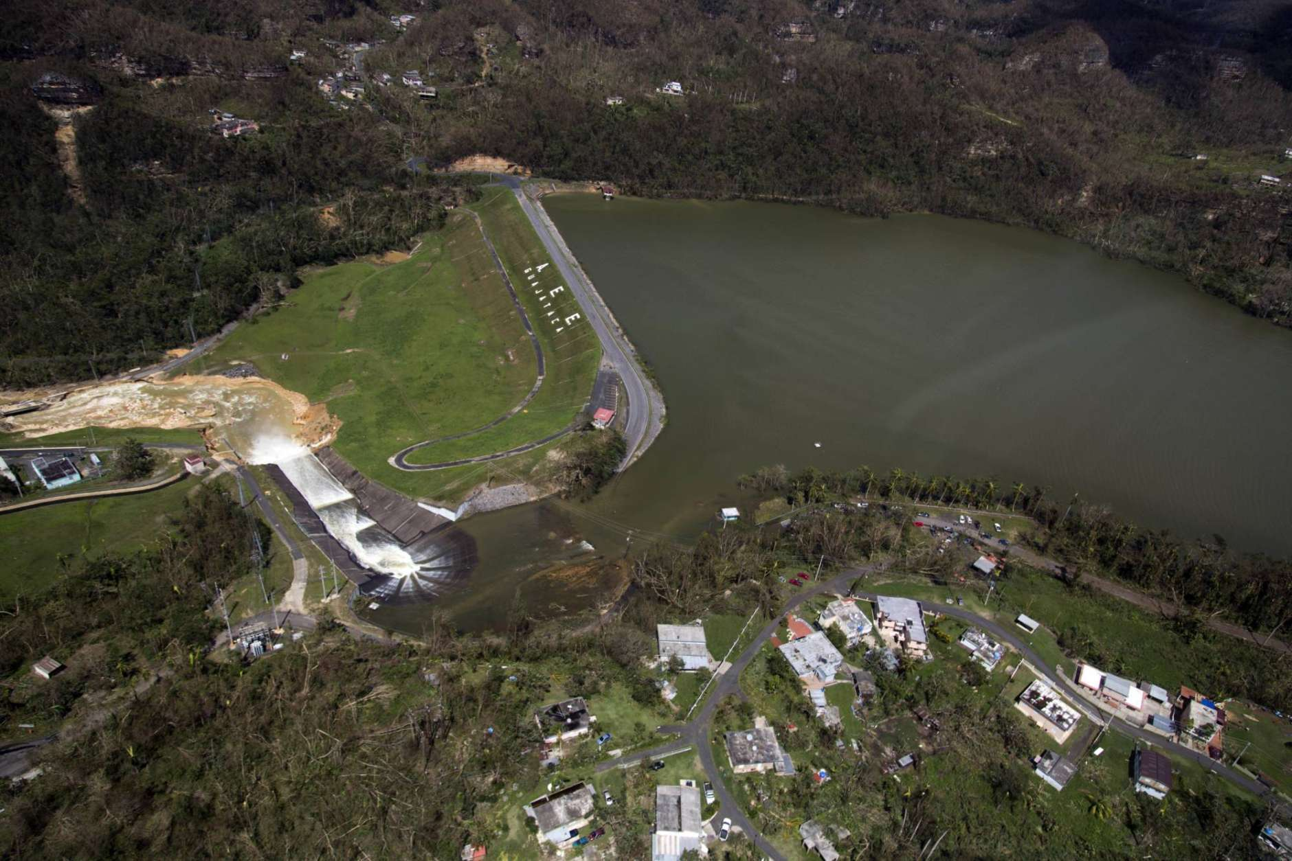Water drains from the Guajataca Dam in Quebradillas, Puerto Rico, Saturday, Sept. 23, 2017. Puerto Rican officials rushed to evacuate tens of thousands of people downstream of the failing dam and the massive scale of the disaster wrought by Hurricane Maria started to become clear. (AP Photo)