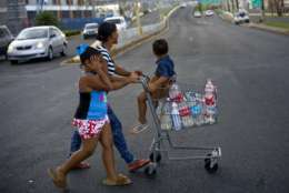 A resident pushes a shopping cart full of recycled bottles filled with water she collected from a water distribution center, in Bayamon, Puerto Rico, Thursday, Sept. 28, 2017. The aftermath of the powerful storm has resulted in a near-total shutdown of the U.S. territory's economy that could last for weeks and has many people running seriously low on cash and worrying that it will become even harder to survive on this storm-ravaged island. (AP Photo/Ramon Espinosa)