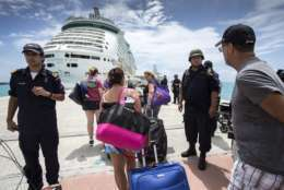 This photo provided by the Dutch Defense Ministry on Sunday, Sept. 10, 2017, shows people walking toward a cruise ship anchored on St. Maarten, after the passage of Hurricane Irma. Irma cut a path of devastation across the northern Caribbean, including this island that is split between French and Dutch control. (Gerben Van Es/Dutch Defense Ministry via AP)