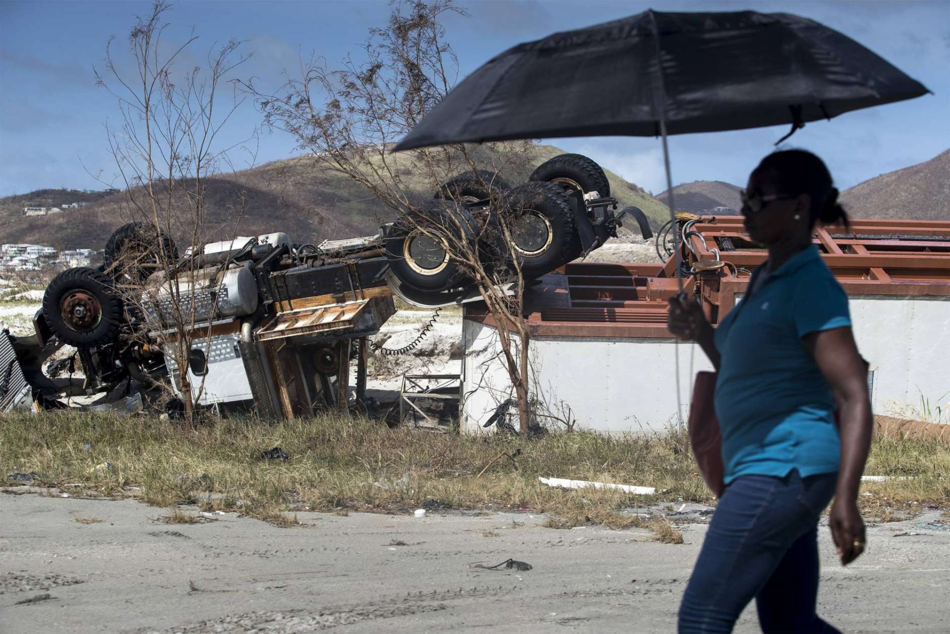This photo provided by the Dutch Defense Ministry shows a woman passing an overturned truck after the passing of Hurricane Irma, in Dutch Caribbean St. Maarten, on Monday Sept. 11, 2017. Dutch King Willem-Alexander said the scenes of devastation he witnessed on the Caribbean island of St. Martin in the aftermath of Hurricane Irma are the worst he has ever seen. (Gerben Van Es/Dutch Defense Ministry via AP)
