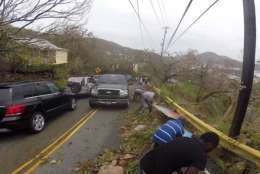 In this image made from video, motorists remove debris caused by Hurricane Irma from the road in St. Thomas, U.S. Virgin Islands, Thursday, Sept. 7, 2017. Hurricane Irma weakened slightly Thursday with sustained winds of 175 mph, according to the National Hurricane Center. The storm boasted 185 mph winds for a more than 24-hour period, making it the strongest storm ever recorded in the Atlantic Ocean. The storm was expected to arrive in Cuba by Friday. It could hit the Florida mainland by late Saturday, according to hurricane center models. (AP Photo/Ian Brown)