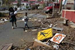 A woman with her two children walk past debris left by Hurricane Irma in Charlotte Amalie, St. Thomas, U.S. Virgin Islands, Sunday, Sept. 10, 2017.  The storm ravaged such lush resort islands as St. Martin, St. Barts, St. Thomas, Barbuda and Anguilla. (AP Photo/Ricardo Arduengo)