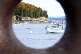 In this Oct. 26, 2013 photo provided by Terry Kole, Bar Harbor, Maine is seen through a rusting boat cleat attached to a dock. The nearby Jordan Pond Shore Trail at the base of Cadillac Mountain in Acadia National Park offers fall colors and a way to get your steps in while enjoying the foliage. (Terry Kole via AP)