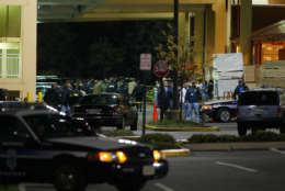 Police officers surround the area next to a Home Depot store near Seven Corners, Va., Monday, Oct. 14, 2002, after a woman was shot and killed in the parking lot. Officials are investigating whether this recent shooting is related to the recent spate of sniper shootings around the Washington area. (AP Photo/Ron Edmonds)