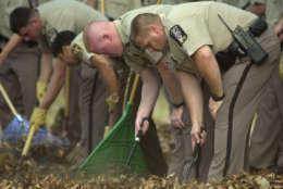 Montgomery County police cadets comb the comb the woods looking for evidence near the Benjamin Tasker Middle School in Bowie, Md., Monday Oct. 7, 2002, after a 13-year-old student was shot and critically wounded as his aunt dropped him off at school. Ballistics tests found Monday that the bullet which struck the boy was identical to those which killed some of the other victims in a series of sniper shootings in the Washington metropolitan area. (AP Photos/Evan Vucci)