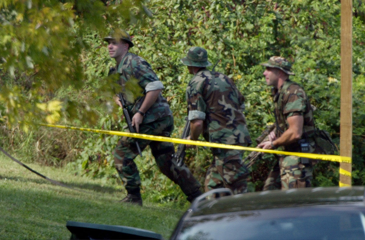 A heavly-armed tactical team walks into the woods around the area near Tasker Middle School in Bowie, Md. Monday, Oct. 7, 2002 near where a 13-year-old boy was shot and critically wounded as his aunt dropped him off at school, bringing fresh terror to the Washington area where a sniper killed six people last week. (AP Photo/J.Scott Applewhite)