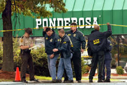 Investigators from the Bureau of Alcohol, Tobacco and Firearms pass under yellow crime-scene tape outside a Ponderosa Steakhouse in Ashland, Va., Sunday, Oct. 20, 2002, where a man was shot Saturday night. Authorities finished a painstaking search around the steakhouse where the 37-year-old man was critically wounded and said Sunday they are assuming the attack is the work of the Washington-area sniper. (AP Photo/J. Scott Applewhite)